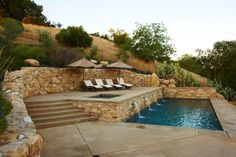 A neutral, stacked stone retaining wall along with the surrounding landscape…
