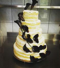 Tort weselny naked cake że świeżymi czarnymi kaliami. Białe biszkopty delikatnie nasączone sokiem owocowym,  przełożone waniliowym musem.