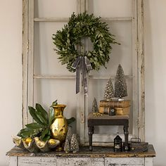 'Tis the season to play up great finds like this vintage window frame and table. Genia dresses up the frame with a boxwood wreath, a group of bottlebrush trees, and a few fresh magnolia leaves. She accents the Christmas spirit by grouping shiny mercury-glass pieces