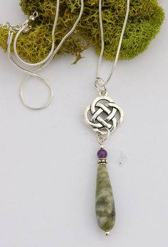 """You don't have to be Irish to love the magical pairing of  Connemara marble and amethyst, suspended from a graceful,  silver-plated quatrefoil Celtic knot. The ancients believed  that Ireland's rare green marble brings serenity and peace,  and that amethyst  increases your spiritual awareness and strength.  Centuries later, the Celts created neverending knotwork as a  sign that life has no beginning and no end. 2 3/4""""l x 3/4""""w  pendant. 18""""l silver-plated snake chain with secure lobster  ..."""