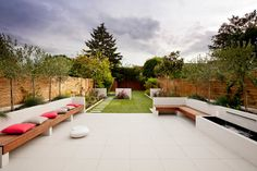 Long town garden great for our long narrow garden space clean white spaces with a pop of colour looks great. love the use of wood for seating and raised borders