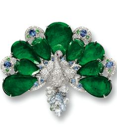 JADEITE, COLOURED SAPPHIRE, RUBY AND DIAMOND 'PEACOCK' BROOCH Designed as a peacock, set with nine pear-shaped jadeites of intense emerald green colour and fine translucency, decorated by circular-cut and pear-shaped sapphires, the body pavé-set with circular-cut diamonds, suspending numerous coloured sapphire briolettes, the sapphires, coloured sapphires and diamonds together weighing approximately 1.25, 7.80 and 1.80 carats respectively, mounted in 18 karat white gold.