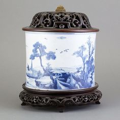 hinese Blue and White Glazed Porcelain Brushpot  Kangxi Period Of wide cylindrical form, the exterior painted with a continual scene of fishermen along a riverbank, the recessed base marked with a single leaf, with fitted wood stand and lid. Height 6 1/4 inches, diameter 7 1/2 inches.
