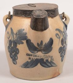 Cowden & Wilcox, Harrisburg, PA Grape Decorated 1 Gallon Stoneware Batter Jug. Circa. 1860-1887. Cobalt blue slip double clusters of 8 grapes flanking the spout and bell flower and leaf decoration on back. Bulbous form with wire bail handle and tin lid and spout cap. 8 1/4 high