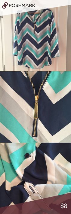Tacera Chiffon Chevron Top Semi-sheer chiffon top with blue, teal white, and gray chevron pattern. Gold half zipper at neckline. Gold zipper detail up the neckline, but zipper close is placed at scoop neck--it does not go all the way up the neck. Top is in EUC. Bust 23, length 29. Tacera Tops Blouses