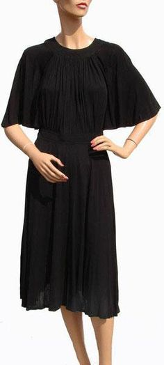 """""""Cape-like sleeves; pleating across centre of bodice; waist is highlighted by a band that fastens with two buttons at the back. Skirt has pleating at sides and back. Back zipper closure; also two buttons at back of neck."""" Designer Vintage Jean Muir Paris Silk Jersey 1960s Black Dress Size M"""