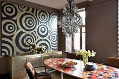 The kitchen's turn-of-the-century French chandelier is suspended above a vintage table purchased in Provence; the decorative panels, executed by Balinese artisans, were inspired by an Aboriginal work, and the sideboard was custom made.