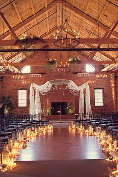 soft look indoor wedding with candle aisle