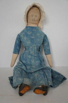 """A very large early cloth doll with an embroidered face, white bonnet and leather shoes. She has little beads for eyes. Her arms are attached and her legs are part of her body but she sits nicely. Her body is an hour glass shape with a broader chest and a slightly smaller hips and a tiny waist. She is stuffed with cotton and has a meduim firm body. She is 25"""" tall. Circa 1880"""