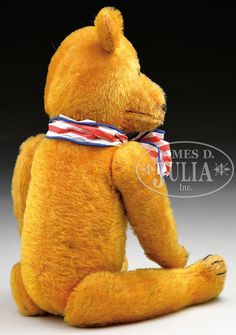 """COLUMBIA TEDDY BEAR BRAND """"LAUGHING ROOSEVELT"""" BEAR. Circa 1907 5-ways jointed teddy bear is excelsior stuffed and made from golden colored mohair. Traditional American style bear with long, thin limbs and proportions with felt paw pads. When stomach is pressed, the mouth opens up to reveal two white teeth. Face is detailed with brown and black glass pupil eyes and hand-embroidered black nose. Three black claws on each paw and foot. Produced as a novelty from a manufacturer in New Y..."""