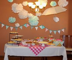 Picnic themed pink & turquoise baby shower - umbrella and tissue paper clouds hanging above the table