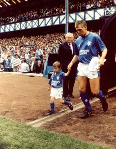 Graham Roberts del Glasgow Rangers (1986-1988) acceder al terreno de Ibrox Park de la mano de un joven seguidor en la 1986/87. Football Stadiums, Football Team, Glasgow, Rangers Fc, Football Pictures, Great Team, Manchester United, Old Photos, Graham