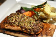 Cedar Roasted Salmon, fresh steelhead salmon with a pine nut parmesan crust, served on a cedar plank with roasted vegetables and herb and feta fingerling potatoes. Delicious!