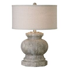 Textured ceramic finished in an antiqued stone ivory accented with brushed aluminum details. The round hardback drum shade is a beige linen fabric with natural slubbing. Materials: Ceramic, metal Sett