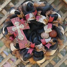 Lovely black deco mesh wreath with a beautiful red cross, decorative balls, burlap ribbon , red ribbon, cheetah ribbon, and glistening bronze ribbon. Love this color combination!