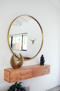 Minimal entryway decor with a large round mirror with gold frame - Decoist