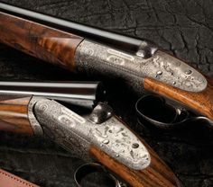 A pair of fine rose and scroll with game scene engraving 20 gauge round action sidelock shotguns by Westley Richards