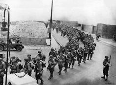 U.S. Army troops march through the streets of an embarkation port on the coast of England, on their way Normandy. | Amazing, Historic Images Of Allied Troops Storming The Beaches Of Normandy On D-Day