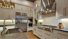 White cabinet kitchen with stainless steel appliances. Stainless steel appliances give an industrial feel to this kitchen. #kitchen #stainlessSteel Geschke Group Architecture.
