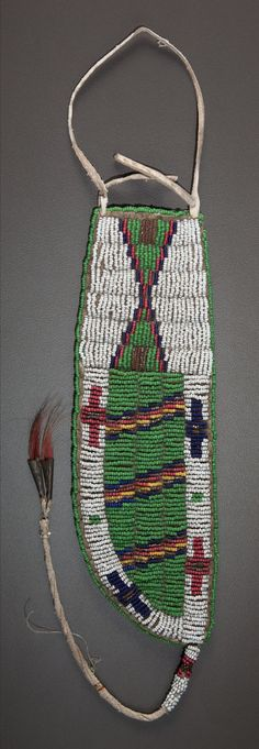A SIOUX BEADED HIDE KNIFE SHEATH  c. 1890    sinew sewn and lane-stitched in classic bead colors, the central panel with diagonal bands flanked on either side by cross motifs, the top panel with a stepped hourglass, a coil beaded thong, trimmed with metal cones inserted with red-dyed horsehair, suspended from the bottom