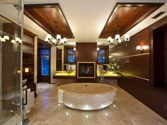 Ultra-luxurious bathroom wraps rich wood paneling around a marble floor, with grand circular soaking tub at center. Embedded floor lighting highlights the tub, while gas fireplace is flanked by four full vanity stations.