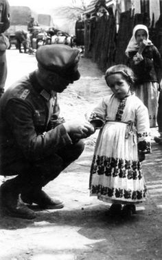 A German officer gives chocolate to a Ukrainian child.