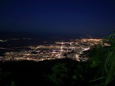 A night view, looking east, of the north end of the Coachella Valley taken from the Mountain Station of the Palm Springs Aerial Tramway on Mount San Jacinto.  Down below you can see the lights of Palm Springs, Cathedral City, Thousand Palms, Rancho Mirage, Palm Desert, Bermuda Dunes, La Quinta, Indio, and Coachella. The string of lights winding their way to the horizon on the right side is Interstate 10 climbing up a 28-mile hill out of the Coachella Valley to Chiriaco Summit.  Much of what…