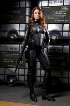 future girl, futuristic look, armor plated boobs, futuristic clothing, sci-fi, girl power, cyber girl, girl with gun, cyberpunk by FuturisticNews.com