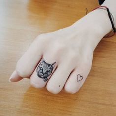 Small cat and tiny heart tattoos on the knucles. Tattoo artist:...