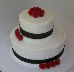 2 tiered monogram red white black butter cream wedding cake | White Two Tiered Wedding cake with black trim and red roses.