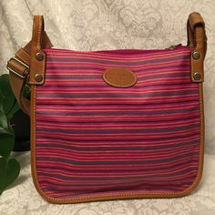"""Fossil Crossbody Beautiful and colorful Fossil Crossbody bag.  Pink vinyl coated bag with stripes in turquoise, black, orange, yellow.  Light brown leather trim and pink cloth interior.  Zip top closure with zipped outer pocket.  One zipped and two open interior pockets.  Long adjustable shoulder strap.  Drop is 13-25"""" Fossil Bags Crossbody Bags"""