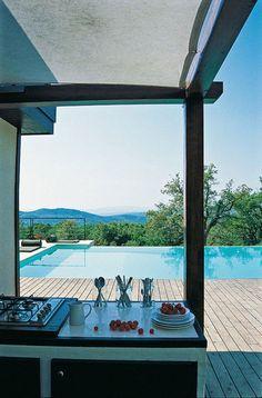 Vanuit de buitenkeuken een prachtig uitzicht over het zwembad dat doorloopt naar het landschap.