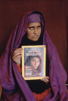 "Sharbat had never seen her famous portrait before it was shown to her in January 2002.  Although her name was not known for 17 years, her picture, titled ""Afghan Girl"", appeared on the June 1985 cover of National Geographic. The image of her face, with a red scarf draped loosely over her head and with her piercing sea-green eyes staring directly into the camera, became a symbol both of the 1980′s Afghan conflict and of the refugee situation worldwide."