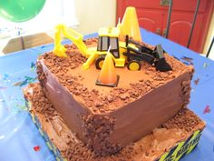 "Backhoe Birthday Cake - This was a square chocolate cake filled with coconut-pecan filling and covered with chocolate buttercream. The cake was decorate with crumbled chocolate cookies, traffic cone candles and a toy backhoe. I created a cake base using a rectangular piece of styrofoam and wrapped the sides with caution tape. The cake board was also frosted with chocolate buttercream and decorated with chocolate ""boulders""."