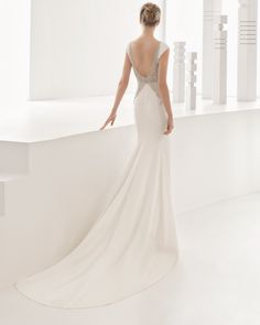 Schmales Kleid aus Crêpe mit U-Boot-Ausschnitt und Rückenverzierungen in Schmetterlingsform mit Strassbesatz in Frost-Optik, naturweiß oder elfenbeinfarben.