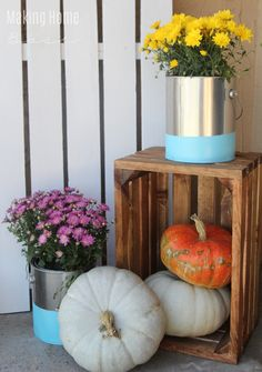 Use empty, clean paint cans to make non traditional planters for your outdoor plants! Paint dipped paint can planters are a great alternative for your porch.