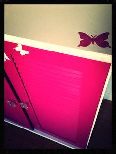 """Commode 2 portes retapée """"girly"""" : couleur cassis, papillons, et poignées fleurs."""