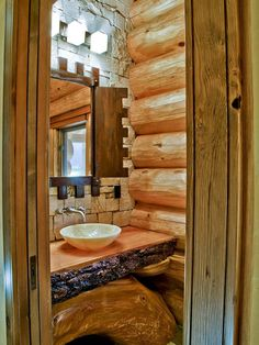 Guest bathroom in a rustic log cabin. Love the stone wall and asymmetrical wood counter.
