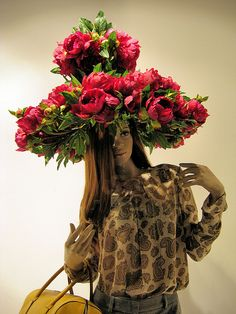 A mannequin sporting a floral hat in a  Brown Thomas window display in Dublin, taken at night.  We sell new and used mannequins and forms at Mannequin Madness so you can create budget friendly window displays like this.