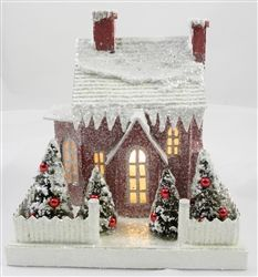 "Glittered Paper Christmas House Celebrate the most joyous season with this holiday cardboard house. Featuring 2 chimneys and a bay window, this snow-draped beauty is smothered in glitter. It has 4 miniature decorated and frosted bottle brush trees. It's yard is surrounded by a corrugated fence. .   5 1/4"" wide x 7 1/2"" long x 7 1/2"" high Light cord included By KD Vintage"