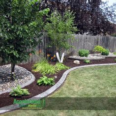 gray concrete curb with a slant and alternate between rock and mulch to add definition and create a fun artistic design along your backyard fence