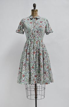 "Vintage 1960s botanical print shirt dress. This vintage floral dress features a small collar, button front, and pleated skirt. Darts in the bust give it a more tailored fit. Unlined. Center hook and eye wouldn't quite close on our 25"" inch waist dress form. size + details 38"" length / 15"" bodice / 34"" bust / 24"" waist"