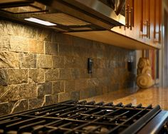 A textured stone backsplash is sure to give your kitchen a rustic look. Here's a tile you can use to create a similar effect: http://americasfloorsource.com/catalog/tile/porcelain/cairo-2580/relic-18072