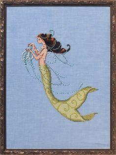 Nora Corbett Tesoro Mia - Cross Stitch Pattern. Model stitched on 32 Ct. Sea Spray linen with DMC floss and Mill Hill beads. Stitch Count: 132W x 156H.