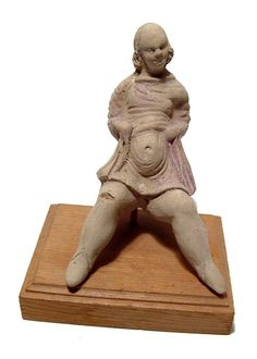 Hellenistic terracotta of pregnant female figure, Canosan, 3rd century B.C. The seated figure wearing a short tunic pulled tightly over her protruding stomach, head tilted slightly to her left, her short hair jaw length, remains of pink pigment and white slip, 10.1 cm high. Private collection