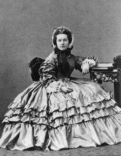 1860s- what an incredibly gorgeous lady! Love the ruffles on her skirt and the huge sleeves! Her bonnet is so neat and lovely!