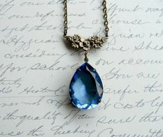 """$40 CA  This oversized brilliant blue crystal pendant necklace features a stunning, multifaceted tear drop shaped jewel as the focal point. Set in an aged brass prong setting, the jewel hangs from a lovely antique brass floral bar on a brass chain for a truly unique, vintage inspired piece perfect for a special occasion. Chain is adjustable in your choice of lengths from 18 to 21"""". Crystal pendant measures 25mm x 18mm (1"""" h). Lobster clasp closure."""
