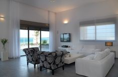 Large white curtains add a touch of class to this living room with high ceiling