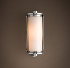 """$189 steel and aluminum •Rotating shade adjusts to focus light  • white-glass cylinder shade  •Uses one 40W max. T10  bulb (included)  Small : 3¼""""W x 4½""""D x 8½""""H  Backplate: 2¾""""W x ¼""""D x 7¾""""H  UL listHardwire.        Dimensions    Small Sconce: 3¼""""W x"""