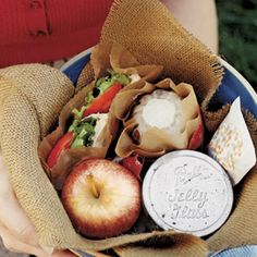 Picnic!!!  a pita sandwich wrapped in paper, a vellum bag filled with crackers, a jelly jar brimming with Lentil and Couscous Salad with Mint, a mini cake baked in a Jell-O mold, and a fresh Gala apple.